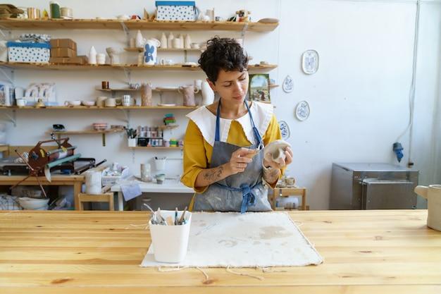 Keramiekstudio professionele vakvrouw die aardewerk van ruwe klei maakt in werkplaats te koop in winkel
