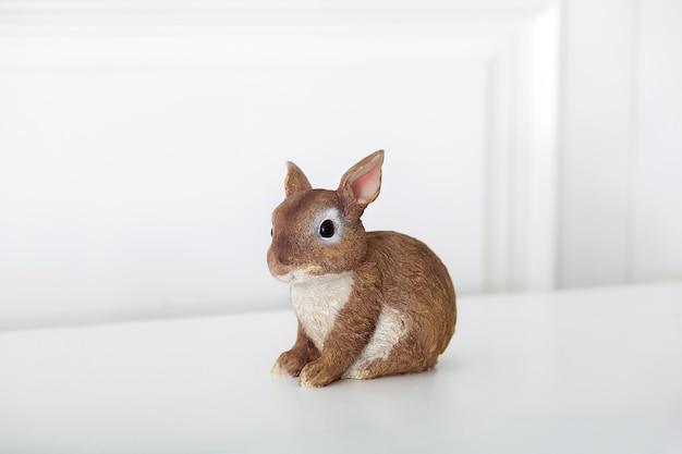 Keramisch beeldje van konijn, geïsoleerd op een witte muur. close-up van bruin beeldje van een paashaas. porseleinen konijntjes. pasen-decoratie - ceramisch pasen-konijn op witte oppervlakte. keramisch konijn