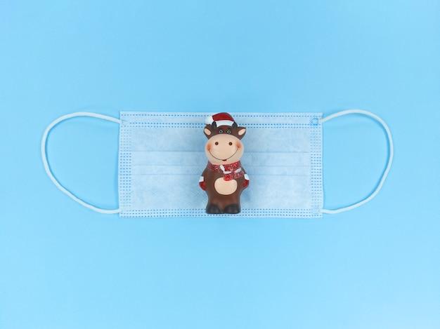 Keramisch beeldje van os op medisch wegwerpmasker op een blauwe achtergrond.