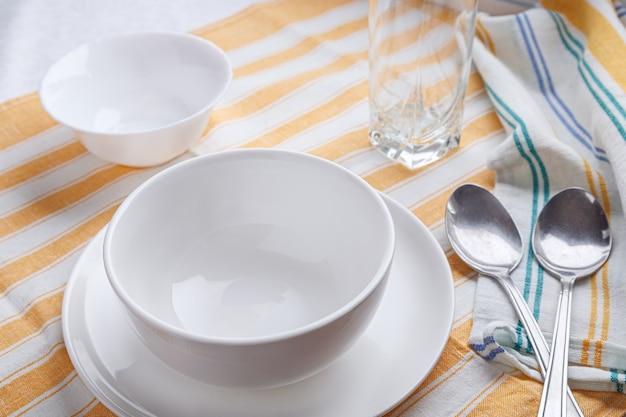 Keramisch serviesgoed voor soep met lepels op tafel geserveerd