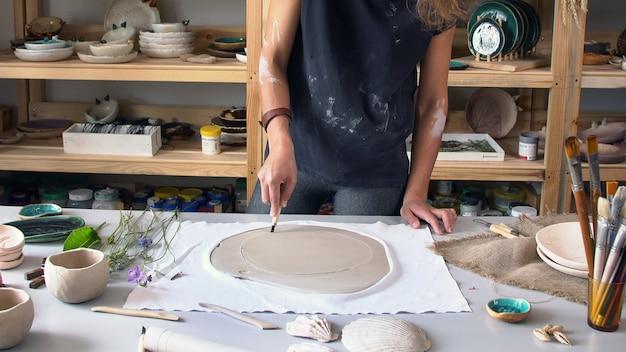 Keramische beeldhouwer maakt een originele tekening op een klei-blank
