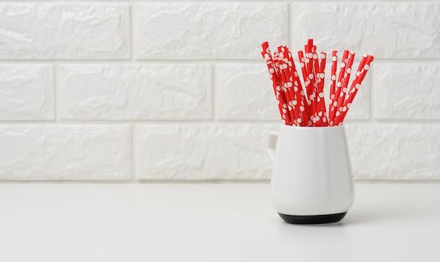Keramische beker met rode papieren cocktailbuizen op witte tafel, witte metselwerkachtergrond