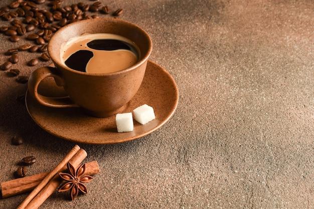 Keramische bruine koffiekop met schotel, suikerklontjes, kaneel en anijs liggen op een stenen achtergrond. er is een plaats aan de rechterkant voor een inscriptie