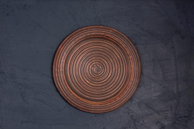 Keramische bruine plaat op een zwart bureau
