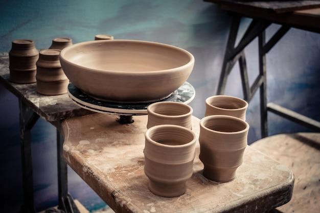 Keramische kleiproducten staan op de plank close-up. beeldhouwer beeldhouwt pottenproducten van witte klei. atelier aardewerk. meester kruik. creativiteit. culturele tradities. handgemaakt. ambacht