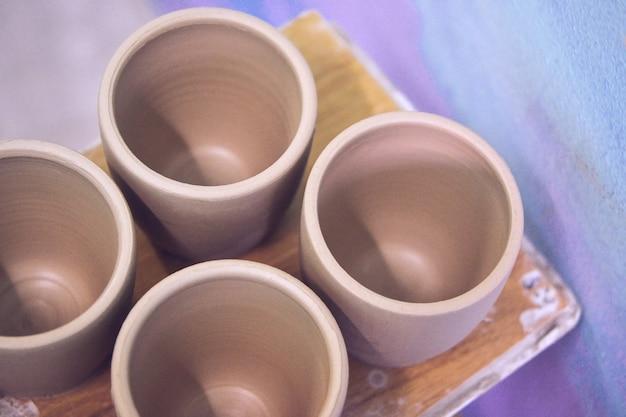 Keramische kleiproducten staan op de plank close-up. beeldhouwer beeldhouwt pottenproducten van witte klei. atelier aardewerk. meester kruik. culturele tradities. handgemaakt. ambacht. gedraaid pottenbakkerswiel.