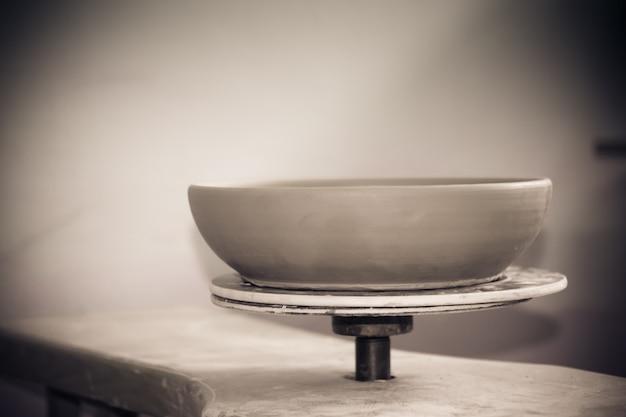 Keramische kleiproducten staan op de plank close-up. beeldhouwer beeldhouwt pottenproducten van witte klei. donker. atelier aardewerk. meester kruik. culturele tradities. handgemaakt. ambacht. gedraaid pottenbakkerswiel.