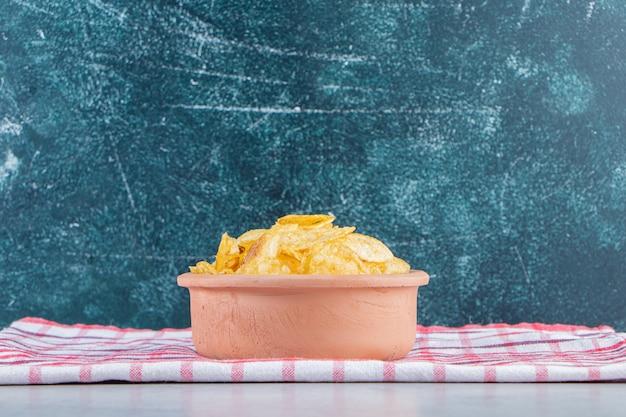 Keramische kom heerlijke knapperige chips op stenen ondergrond.