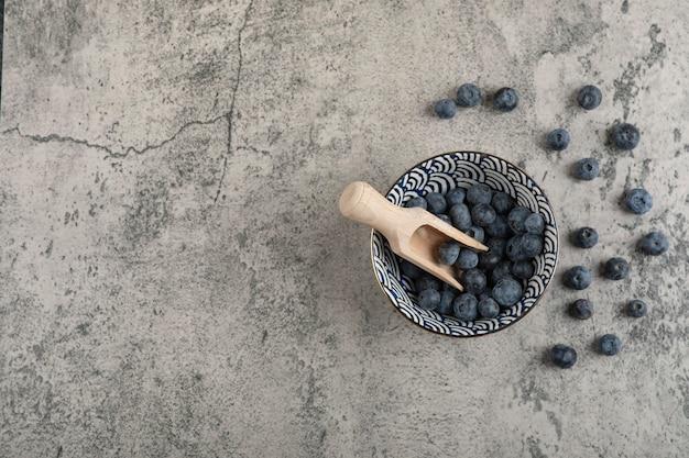 Keramische kom heerlijke verse bosbessen met houten lepel