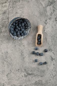 Keramische kom heerlijke verse bosbessen op marmeren oppervlak
