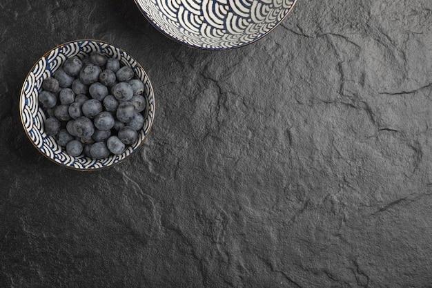 Keramische kom heerlijke verse bosbessen op zwarte ondergrond