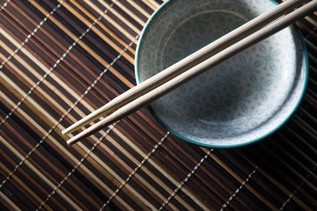 Keramische kom met eetstokjes op bamboe achtergrond