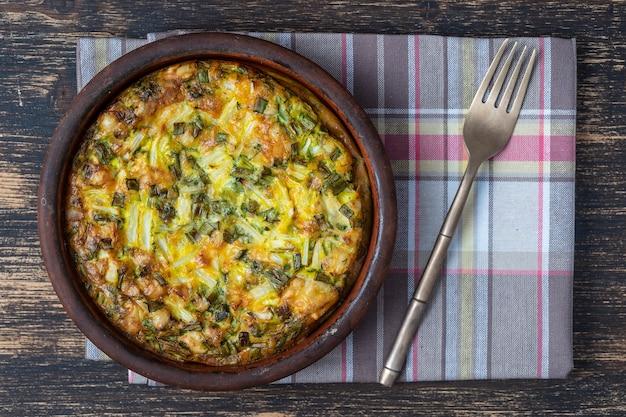 Keramische kom met plantaardige frittata, eenvoudig vegetarisch eten. frittata met ei, paprika, groene uien en kaas op tafel, close-up, bovenaanzicht. gezonde ei-omelet