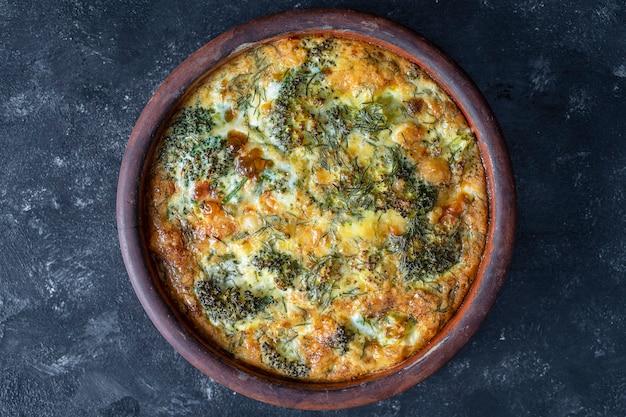 Keramische kom met plantaardige frittata, eenvoudig vegetarisch eten. frittata met ei, paprika, ui, broccoli en kaas op houten tafel, close-up. italiaanse eieromelet