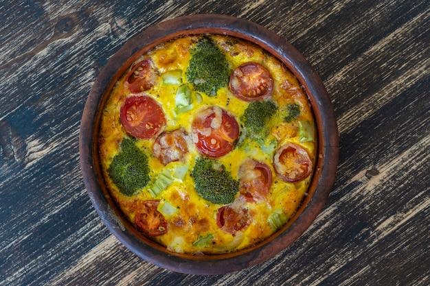 Keramische kom met plantaardige frittata, eenvoudig vegetarisch eten. frittata met ei, tomaat, paprika, ui, broccoli en kaas op houten tafel, close-up. italiaanse eieromelet