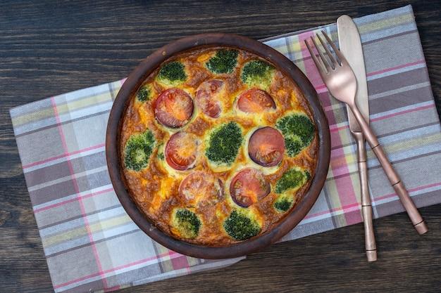 Keramische kom met plantaardige frittata, eenvoudig vegetarisch eten. frittata met ei, tomaat, paprika, ui, broccoli en kaas op houten tafel, close-up. italiaanse omelet