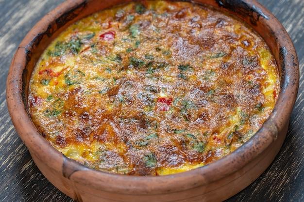 Keramische kom met plantaardige frittata, eenvoudig vegetarisch eten. frittata met tomaat, paprika, ui en kaas op houten tafel, close-up. italiaanse eieromelet, bovenaanzicht