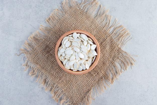 Keramische kom met rauwe pompoenpitten op stenen ondergrond.