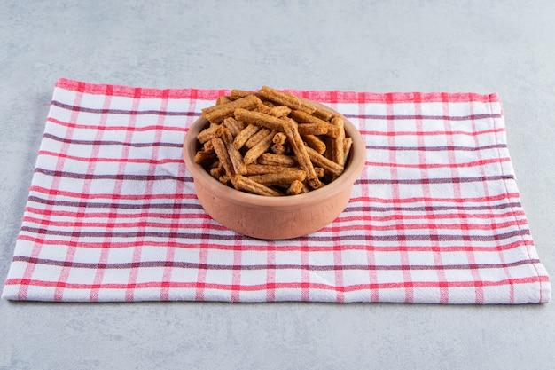 Keramische kom smakelijke knapperige crackers op stenen achtergrond.