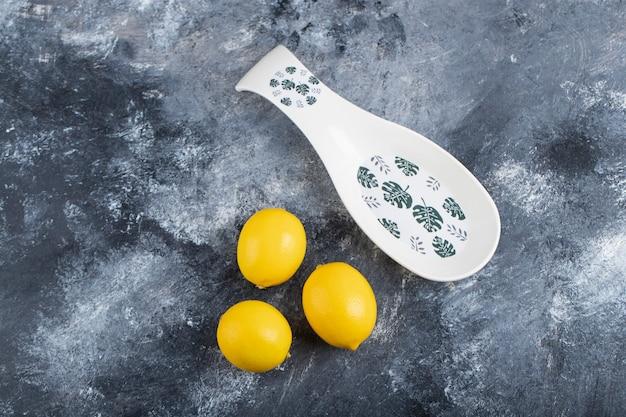 Keramische kom van drie sappige rijpe citroenen geplaatst marmeren oppervlak