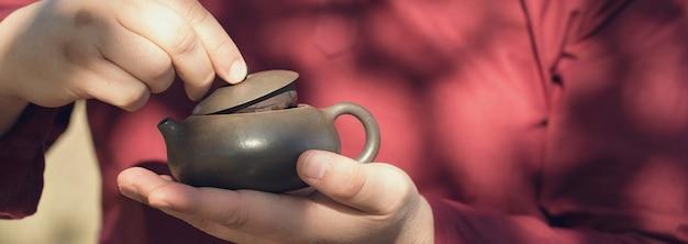 Keramische kommen gemaakt van klei op een houten ondergrond. de man drinkt chinese thee.