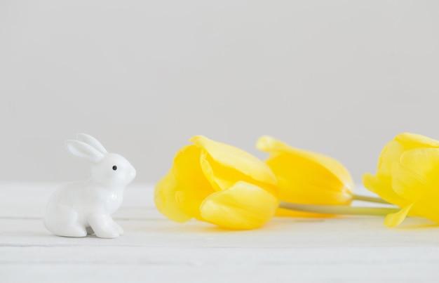 Keramische konijnen en gele tulpen op witte houten achtergrond