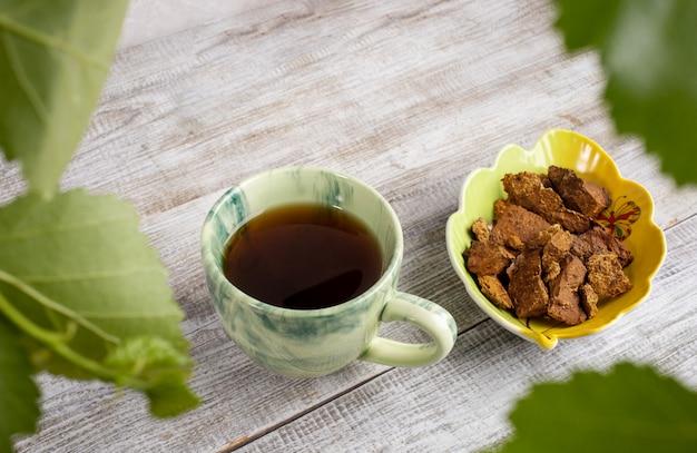 Keramische kop van genezende drank van berkenchampignon chaga, kom van paddestoelstukken op lichte houten achtergrond. kopieer ruimte.