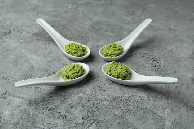 Keramische lepels met wasabi op grijze gestructureerde achtergrond