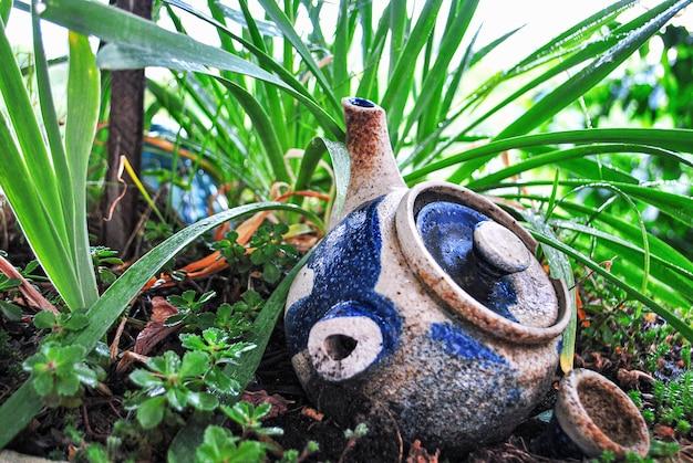 Keramische oude theepot op de grond in een bloembed.