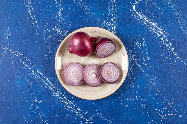 Keramische plaat met paarse uienringen op marmeren oppervlak
