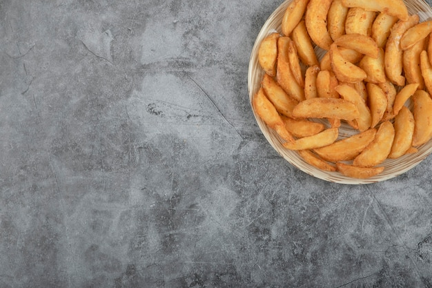 Keramische plaat van smakelijke gebakken aardappelpartjes op stenen achtergrond.