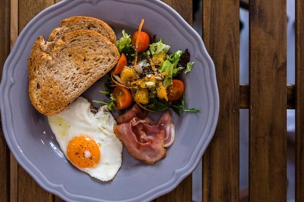 Keramische plaat van toast; gefrituurd ei; spek en salade op keramische plaat over het houten bureau