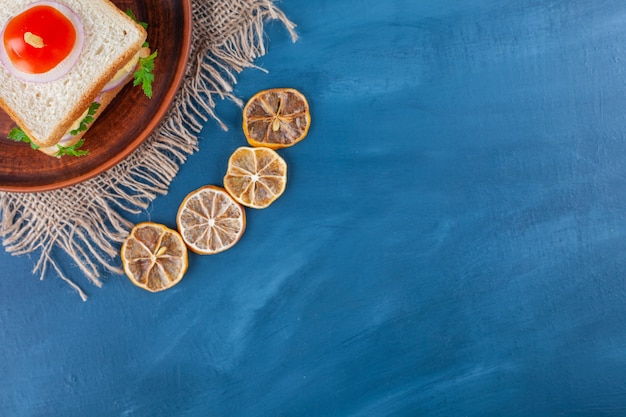 Keramische plaat van zelfgemaakte plantaardige toast op blauwe ondergrond.