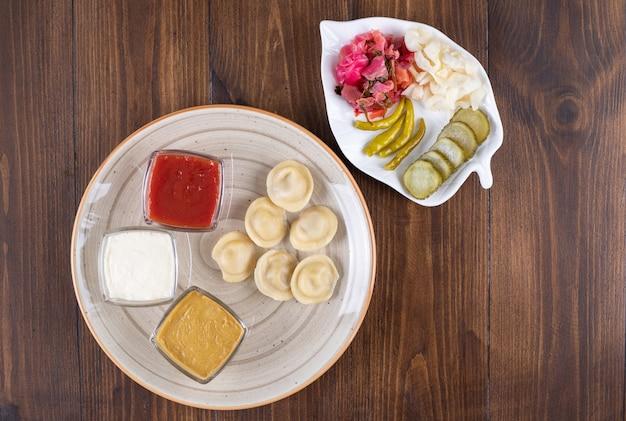 Keramische plaat vol met zelfgemaakte dumplings en augurken op houten oppervlak.