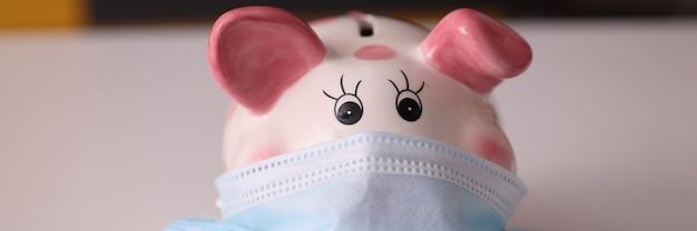 Keramische spaarvarken in beschermende medische masker bedrijfsontwikkeling in coronavirus