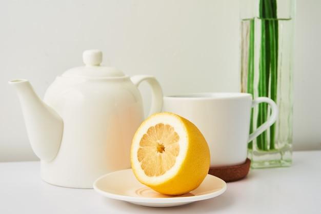 Keramische theepot kopje thee met citroen en bloemen in vaas op witte achtergrond keuken interieur theetijd concept