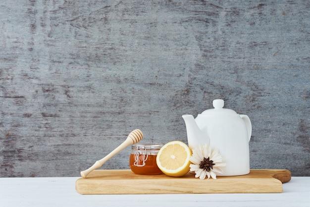 Keramische theepot, witte kop, honing in een glazen pot en citroen op houten