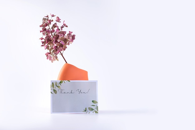 Keramische vaas met gedroogde bloemen en een poster voor tekst geïsoleerd op een lichte achtergrond, close-up