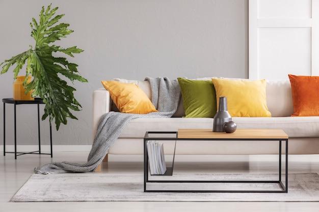 Keramische vazen op eenvoudige houten salontafel in stijlvolle woonkamer met grote comfortabele bank met kleurrijke kussens, echte foto met kopieerruimte aan de muur