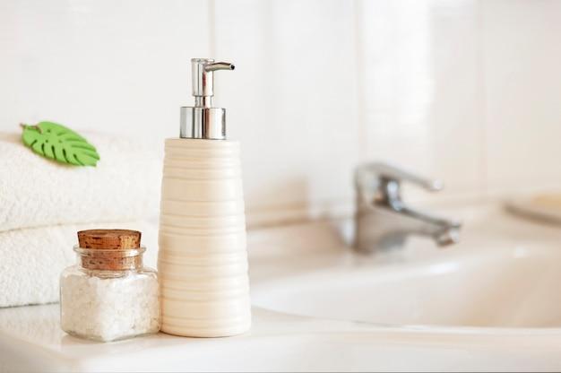 Keramische zeep, shampoo fles, glazen fles met badzout en witte katoenen handdoeken op wazig interieur van de badkamer met wastafel en kraan.