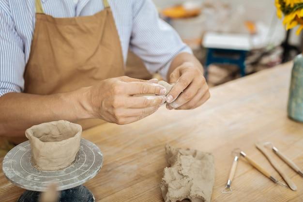Keramist en items. keramist die bruine schort draagt die aan de houten werktafel zit die kleine voorwerpen vormt