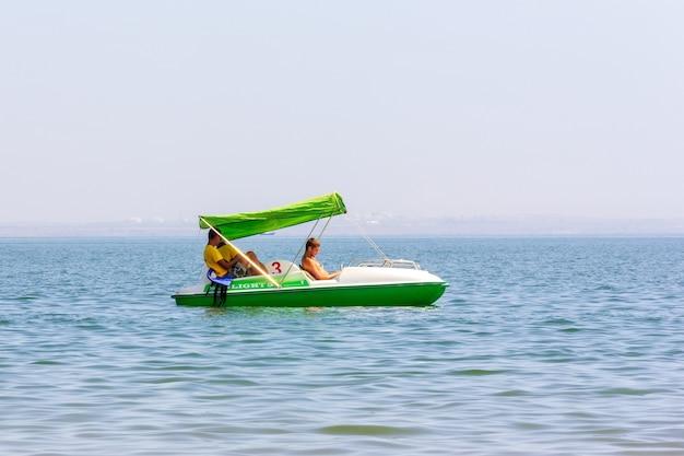 Kerch, rusland - 13 augustus 2019: drie jonge badmeesters op een witte en groene catamaran drijven langzaam op het zeewater op een zomerdag