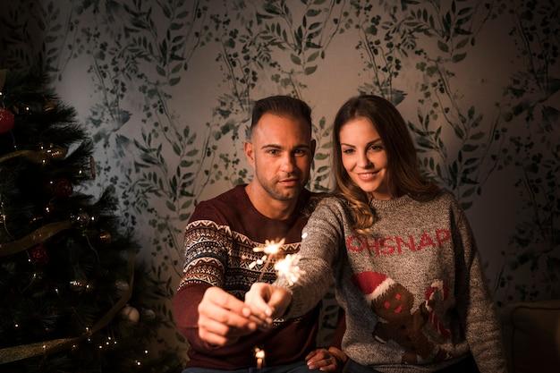 Kerel dichtbij dame met bengalen steekt dichtbij kerstboom aan