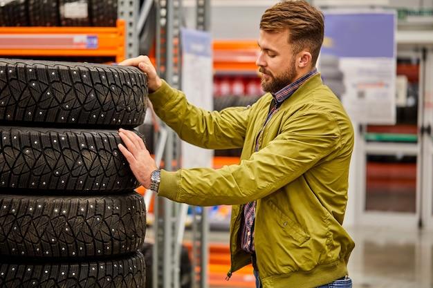 Kerel die autoband in opslag kiest, kaukasisch mannetje wil wielen voor auto kopen, het assortiment onderzoeken