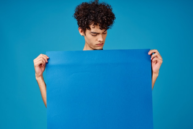 Kerel die blauwe banneradvertentie houdt
