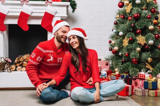 Kerel die dame koesteren dichtbij kerstboom
