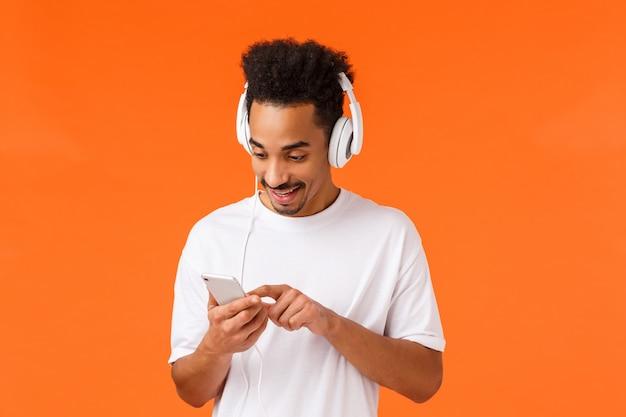 Kerel die de juiste weg zoekt, verhoogt de stemming. blije aantrekkelijke afro-amerikaanse man in wit t-shirt, koptelefoon op, bladerend door afspeellijst in smartphone glimlachen, muziek luisteren, oranje