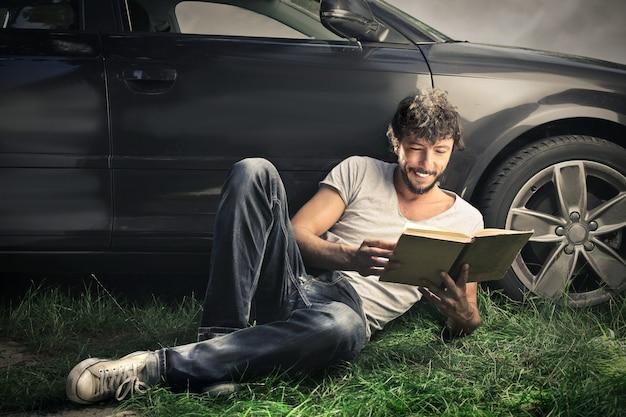 Kerel die een boek naast zijn auto leest