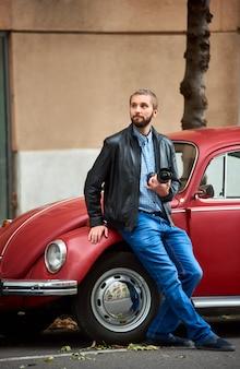 Kerel die een camera in hand houdt die zich dichtbij een rode retro auto bevindt die de afstand onderzoekt