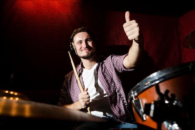 Kerel die een drumstick houdt en duimen opgeeft
